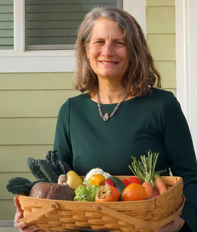 Rev. Beth Love with basket of fruit and veggies